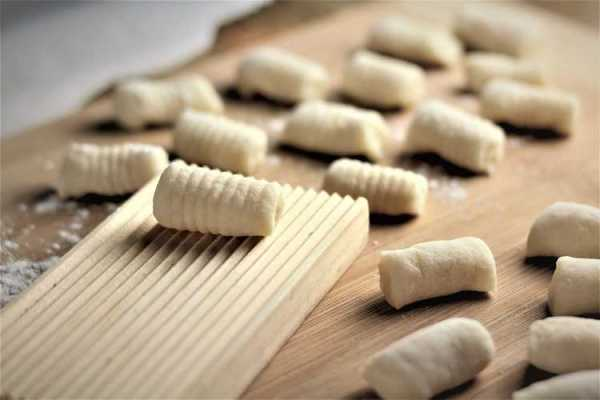 gnocchi board with a rolled gnocchi on it surrounded by other individual gnocchi