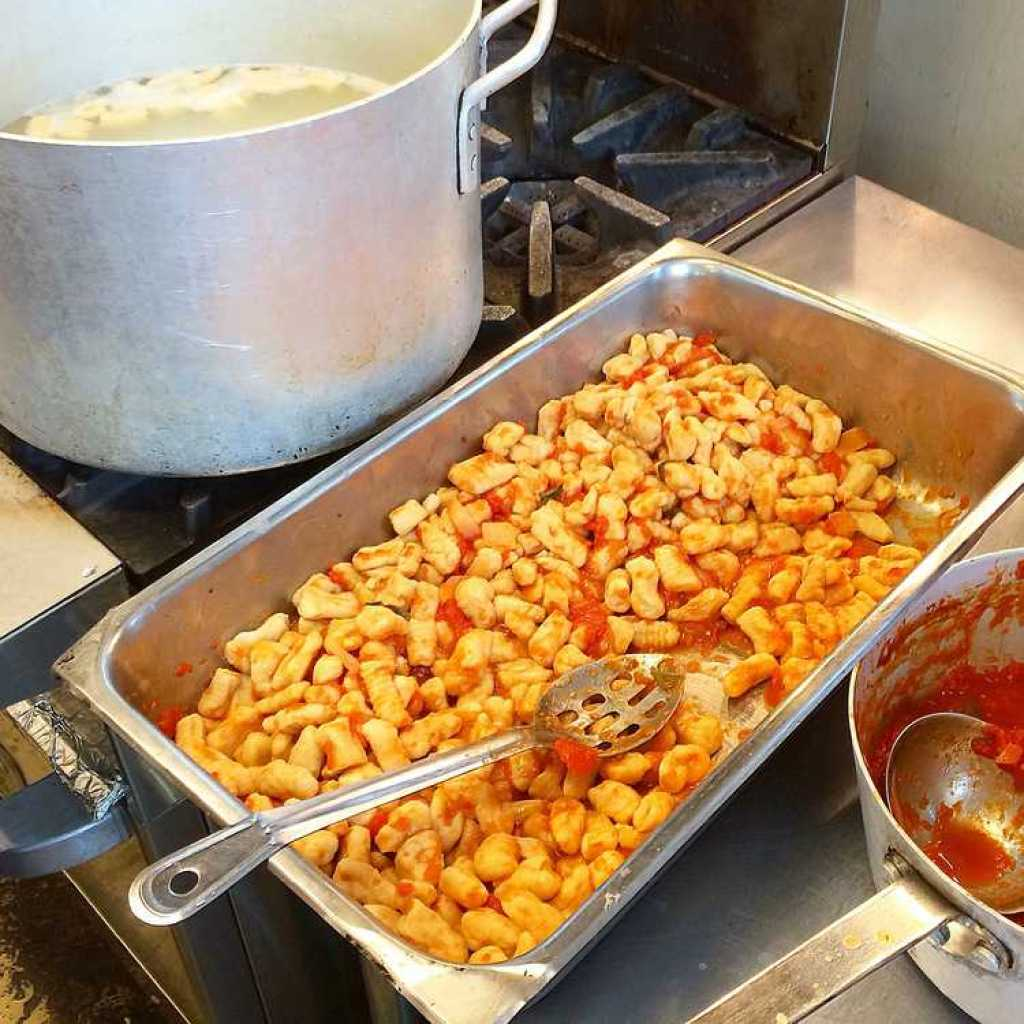 large pot of boiling water next a pan filled with cooked gnocchi in tomato sauce