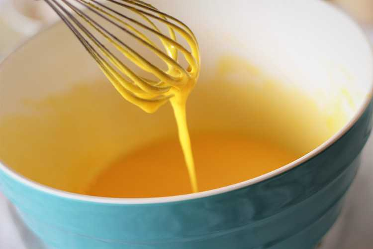 whisking eggs in mixing bowl with whisk for nonna's sponge cake