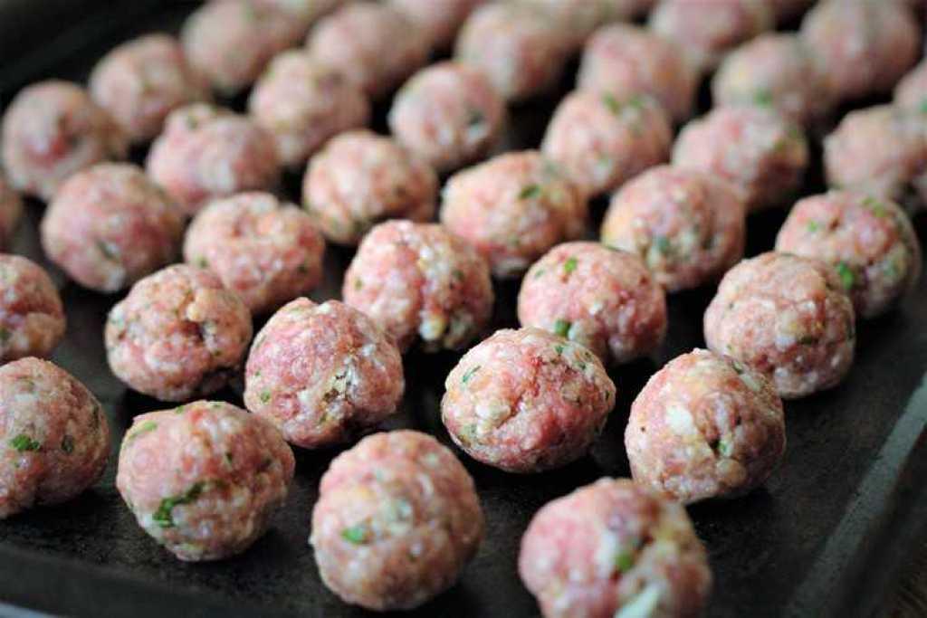 little raw meatballs on baking sheet