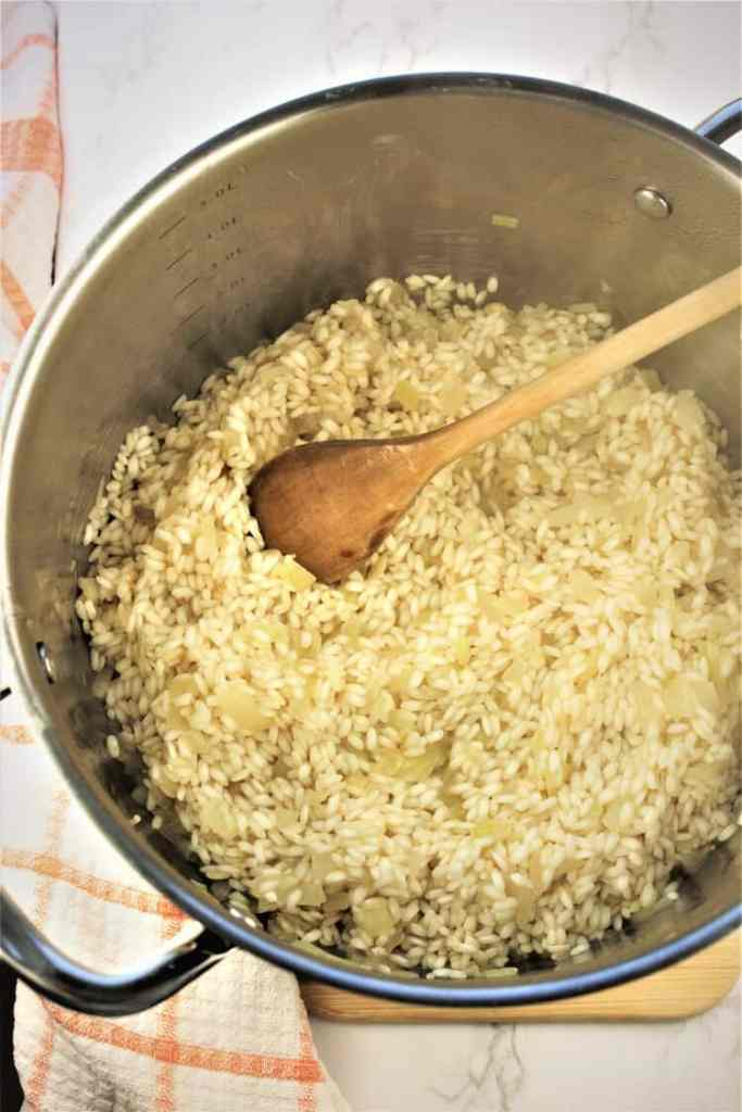 risotto being stirred with wooden spoon in saucepan