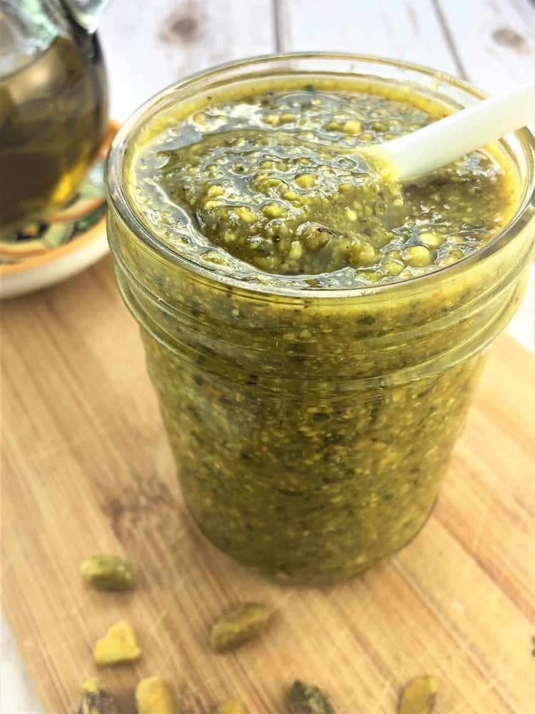 glass jar filled with pistachio pesto with spoon in it