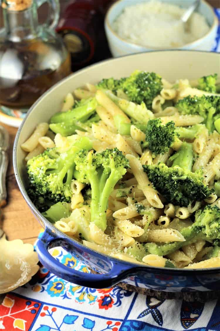 blue pan filled with pasta and broccoli with olive oil bottle and bowl of cheese in background