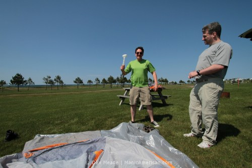 Two guys setting up a tent. One is brandishing a mallet.