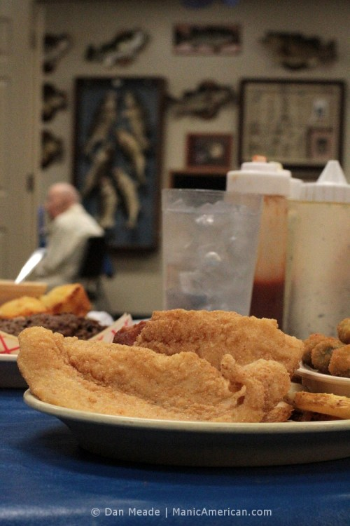 A plate of catfish in the foreground, a man before a wall of fish in the back.