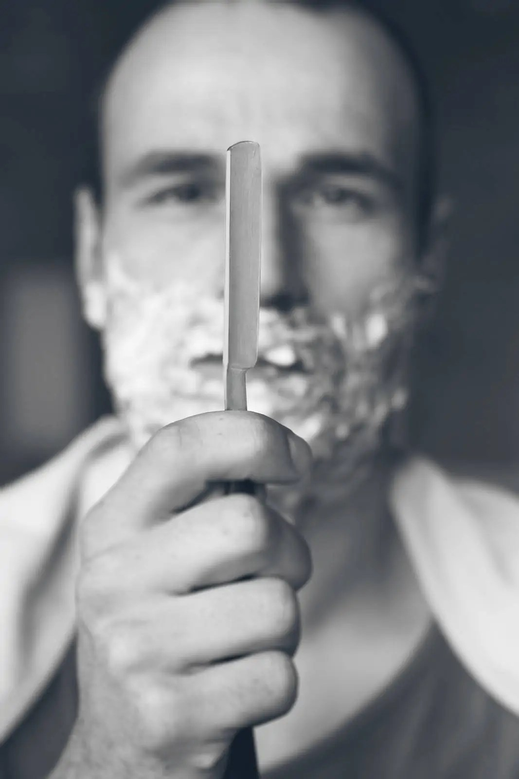 Young Man Holding Straight Razor. Black And White