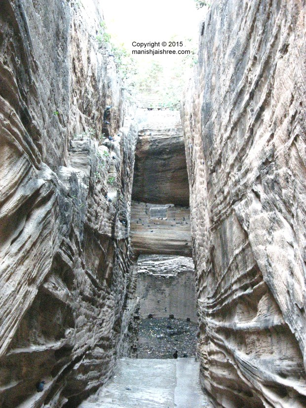 Impressive adi kadi vav with a small window above the well-shaft, littered with plastic and debris and dying a slow death, Uparkot, Junagarh