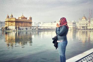 A girl praying in Golden Temple