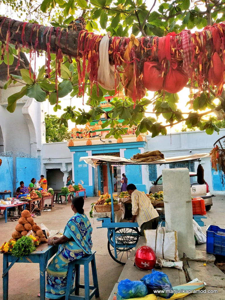 fruit vendors selling raw mango and coconut outside Visa temple