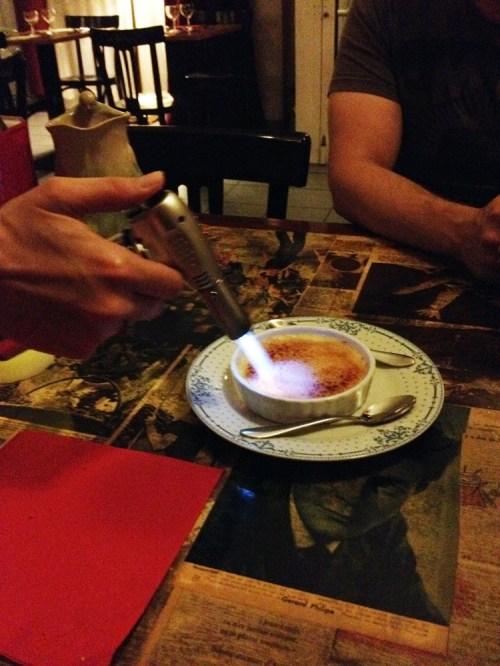 Crème brûlée karamellisoitiin pöydässä.
