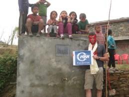 La fontaine-réservoir avec sa plaque au nom de l'association MANOJ. Financement par la Fondation SAUR
