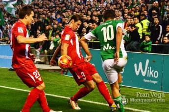 Ceballos saca la pelota entre dos contrarios (Betis-Sevilla 15/16)