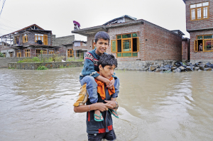 A Kashmiri boy carrying his little brother to higher ground