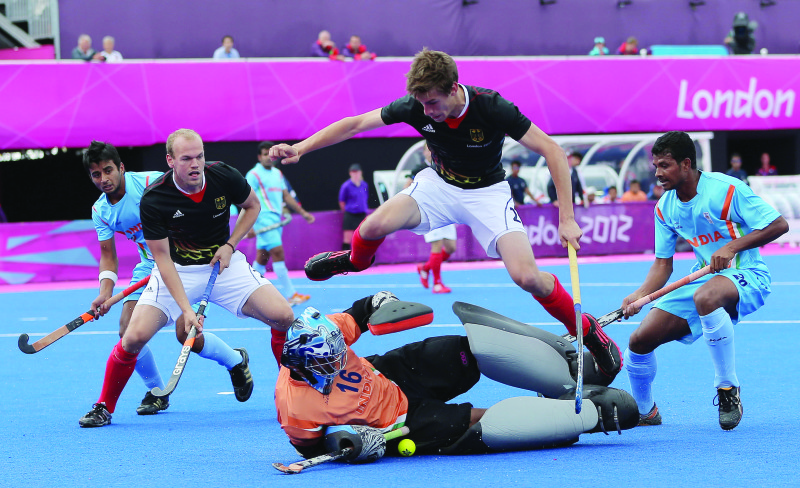 Germany's Florian Fuchs (top) fights for the ball with Goalkeeper Sreejesh Parattu Raveendran of India during Men's field hockey preliminary round match against India at Riverbank Arena during the London 2012 Olympic Games, London, Britain, 03 August 2012