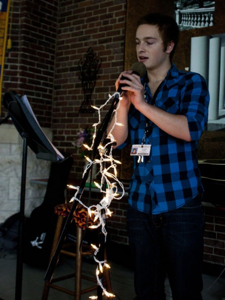 """Christian Dospil (11) is the first participant to read during the Open Mic Night; here, he is reading an original poem entitled """"Fireflies."""" 