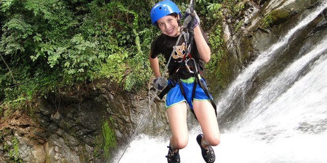 Young girl rappelling beside a waterfall