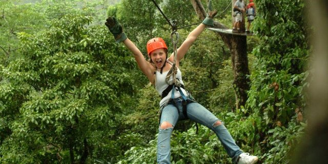 Girl zip lining through jungle canopy