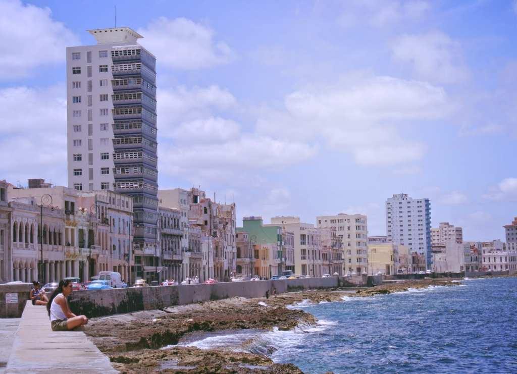 a woman sitting by the sea on Havana's Malecon