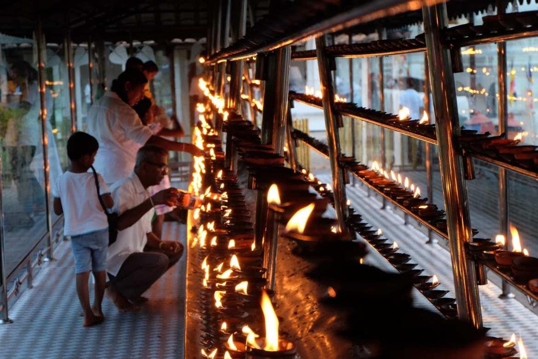worshippers lighting candles in Kandy, Sri Lanka