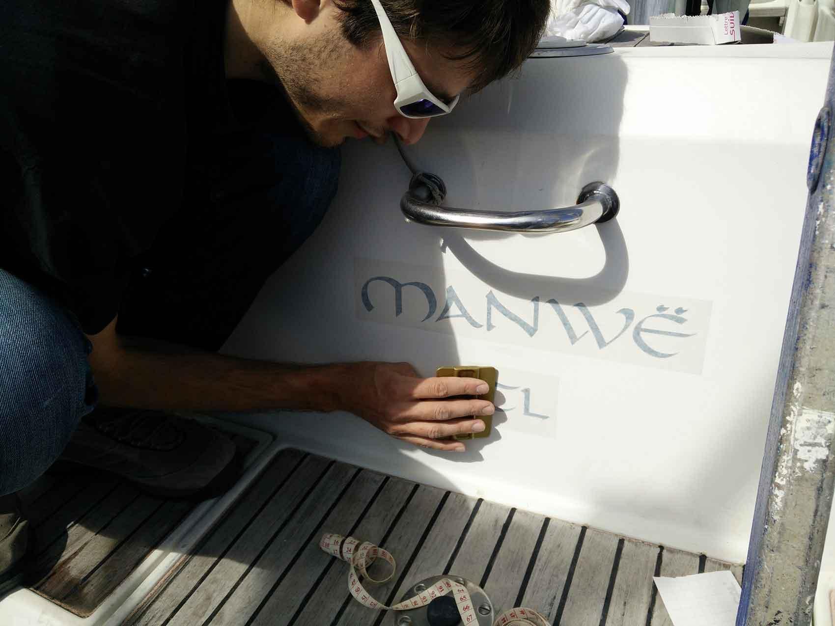 Damien appuie pour coller le nouveau nom du bateau.