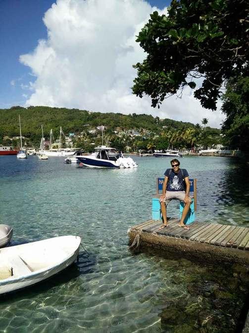 Damien assis près d'un ponton d'annexe, sur la jetée de Port Elizabeth à Bequia.