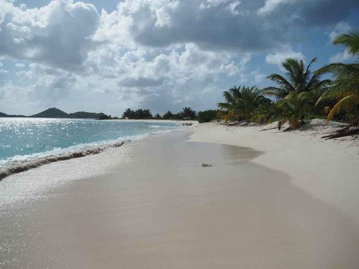 Plage de sable blanc et ressac d'eau turquoise aux Caraïbes.