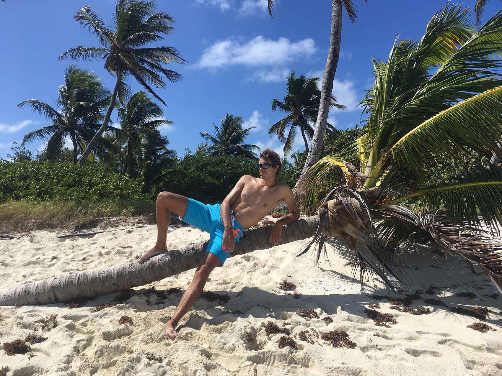 Damien sur un cocotier sur l'île de Petit Tabac.