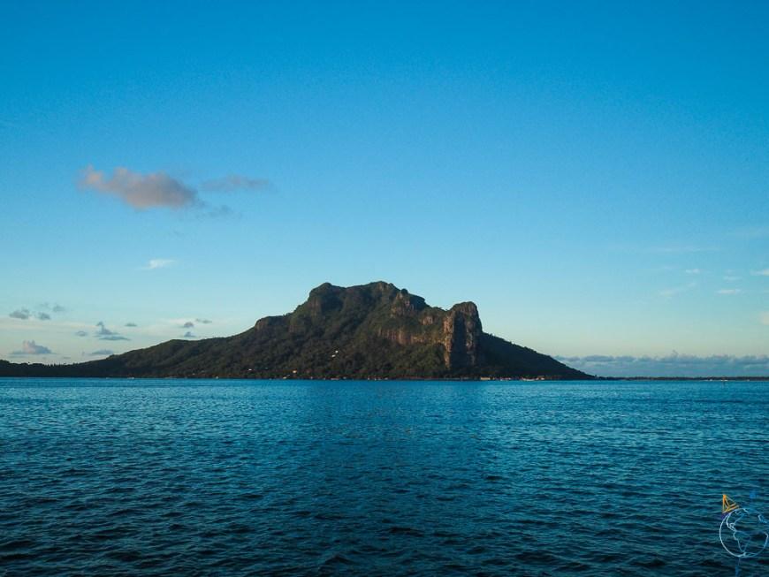 L'île de Maupiti éclairée par les rayons du soleil couchant.