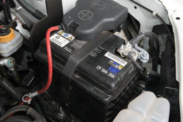 Repare a porca de fixação da bateria no centro em baixo no final da correia.