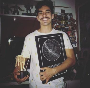 homem segura quadro fundo preto do mapa do meu ceu e na outra mão um troféu