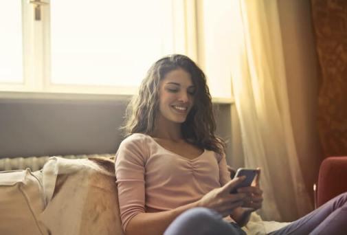 garota olha para celular sorrindo, ilustrando um namoro à distância
