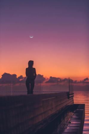 lua na astrologia - mulher pensativa em pier ao por do sol