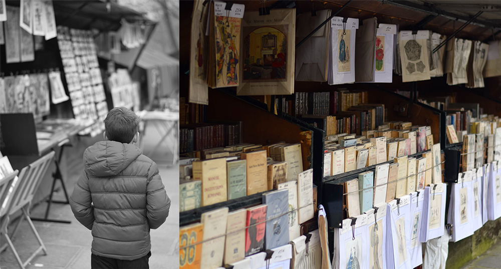 Photo of boy walking along the Seine looking at books.