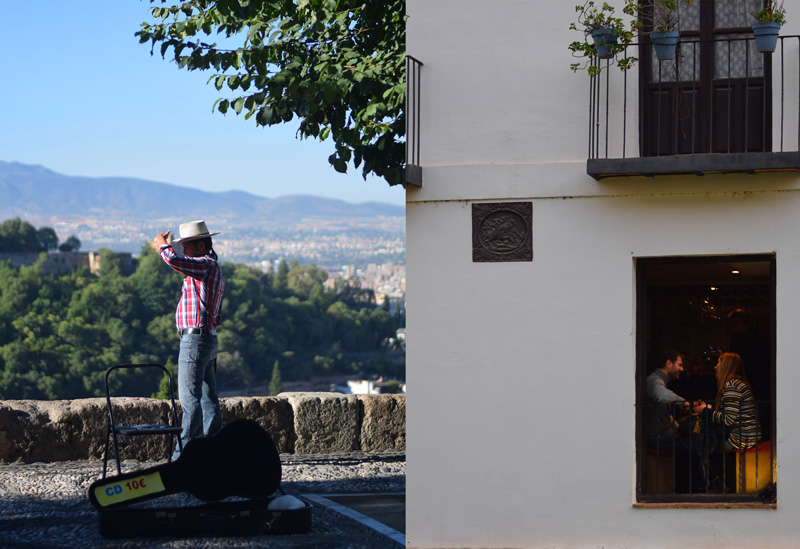 Image of Granada Spain travel including a musician in the Mirador de San Nicolas and a couple having drinks in the lower Albaicin