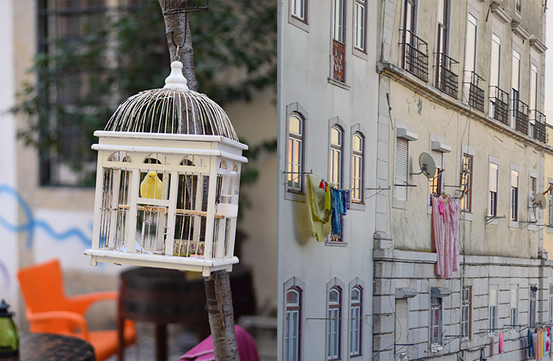 A birdcage in a plaza in Lisbon next to laundry hanging on a beautiful old building.