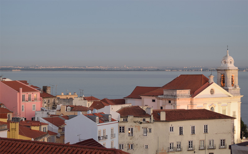 Sunset in Lisbon, Portugal. The sun is casting a warm glow over the city's buildings.