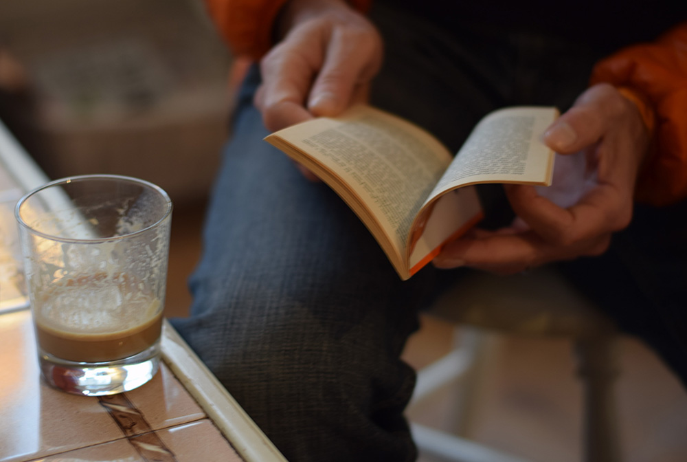 A close up photo of a glass of coffee and a man reading a small book in the Krog of Krinkel Bokcafe in Bergen, Norway