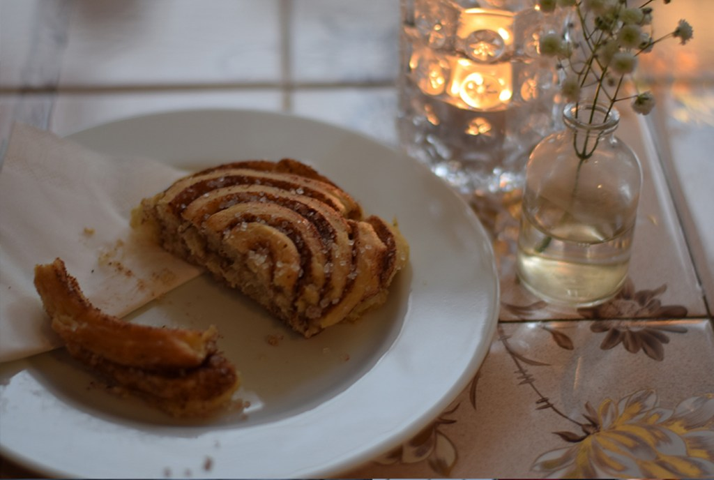 Photo of a cinnamon roll on a plate next to a candle in the Krog og Krinkel Bokcafe in Bergen, Norway.