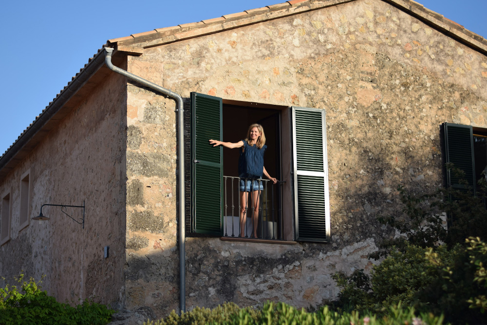 Woman standing at window of Mallorcan farmhouse.