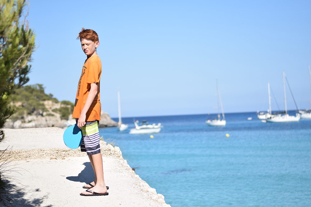 A teenager standing next to a beautiful harbor with sailboats in Mallorca, Spain.
