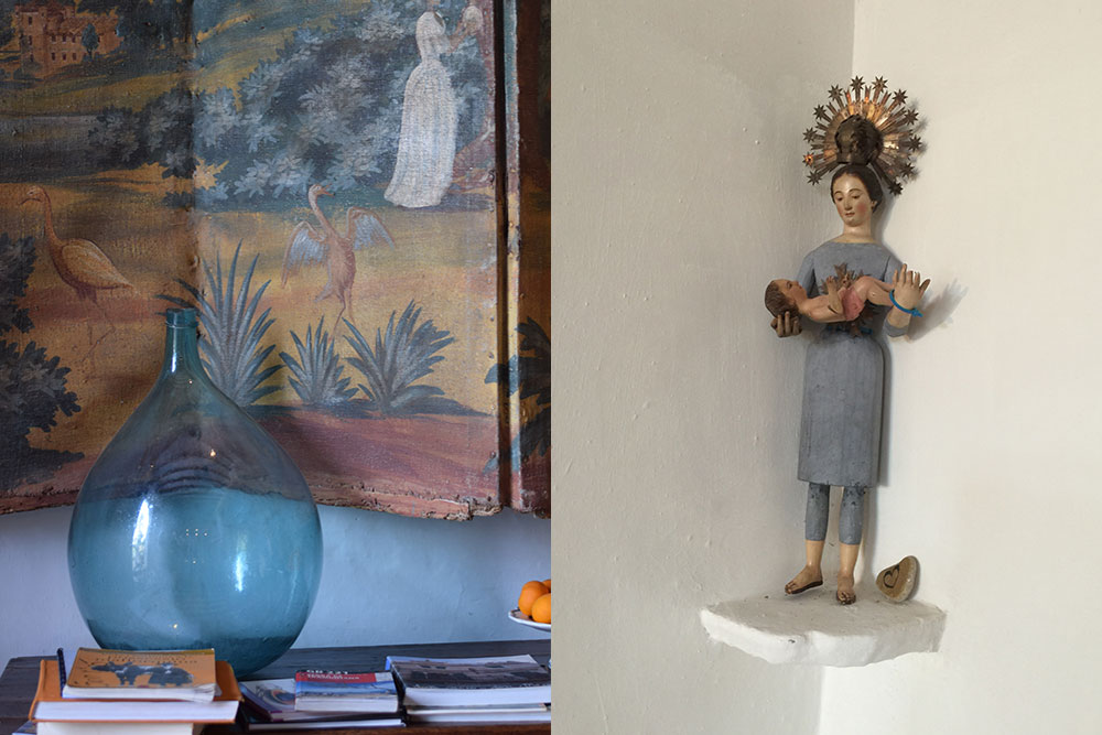 Interior detail of a blue glass bottle on a table with guidebooks, a traditional painting and a religious statue of a women holding a baby.