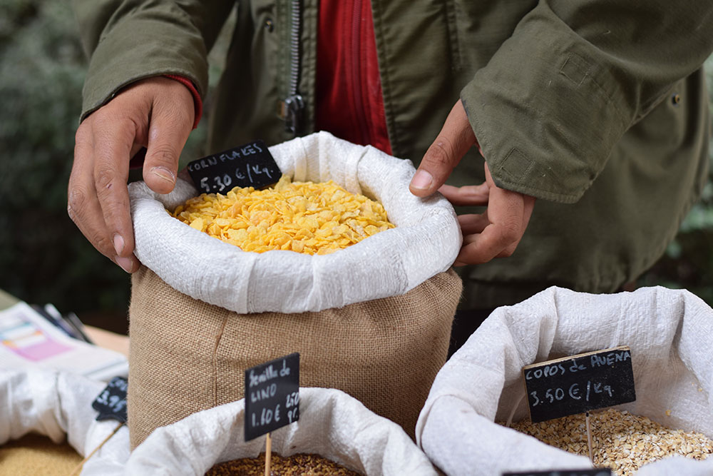 Photograph of a seller holding a burlap bag of bulk cereal at the Santa Maria market in Mallorca, Spain.
