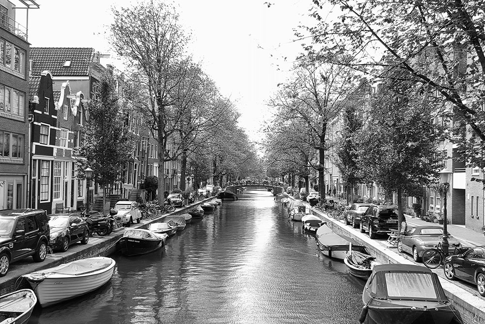 A black and white photo of a canal in Amsterdam lined with boats and cars.