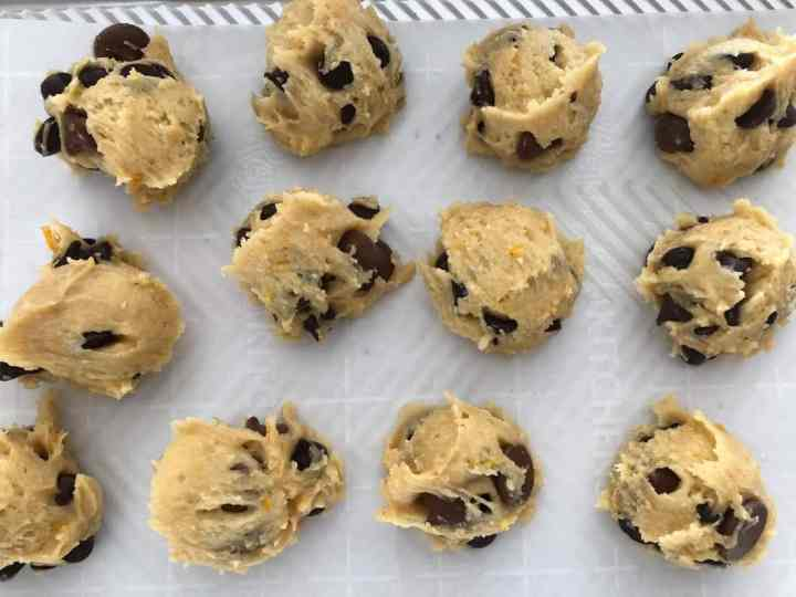 scoops of cookie dough on sheet pan