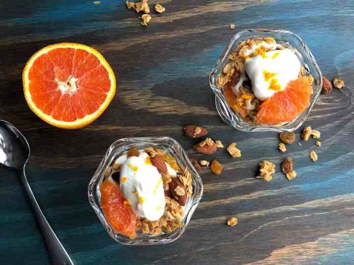 Two Orange Granola Parfaits on a table with half an orange