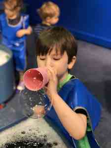 boy blowing bubbles boston children's museum