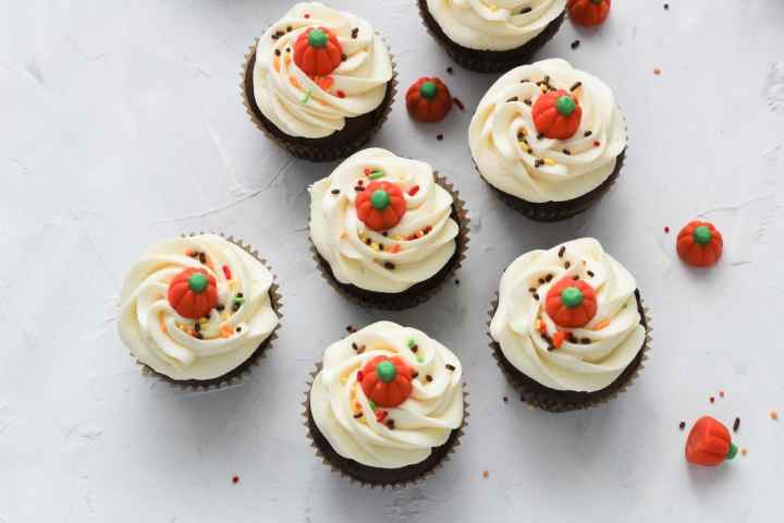 chocolate cupcakes with vanilla buttercream on white concrete