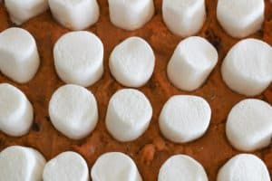 adding marshmallows to sweet potato souffle