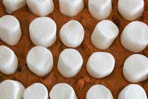 adding marshmallows to sweet potato souffle