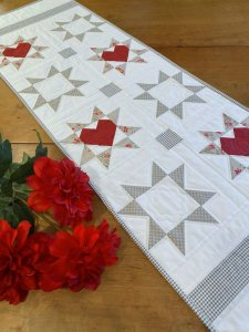 Love and Wishes Table runner on wooden table with flowers